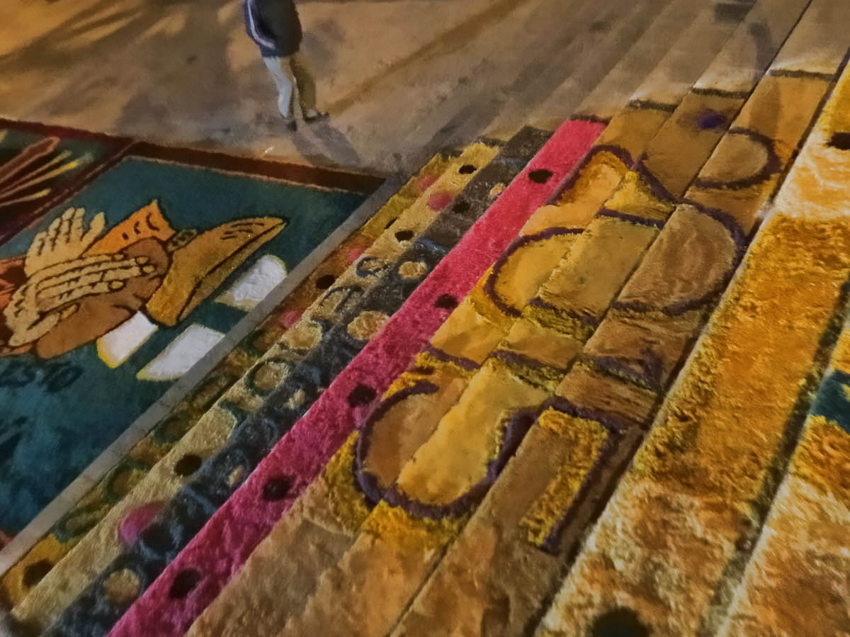 This sawdust carpet is created as a way to pay penance/homage to the patron saints.   (Note feet of person in top of photo for size perspective.)