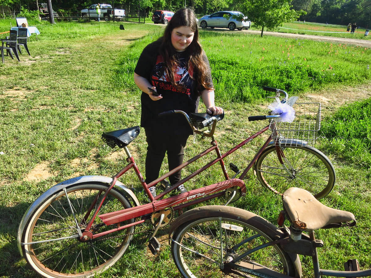 Hannah admires a bicycle built for two at the Bluebonnet Flea Market.