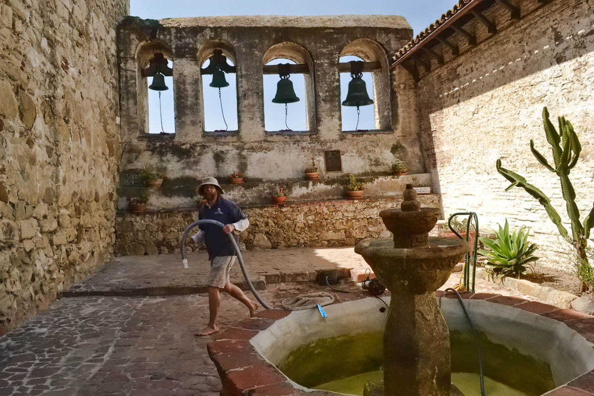 A volunteer cleans the fountain.