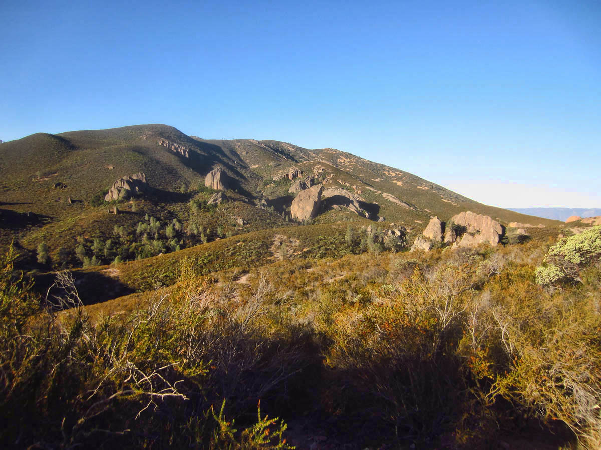 The area is predominantly rolling hills, with large boulders scattered about.