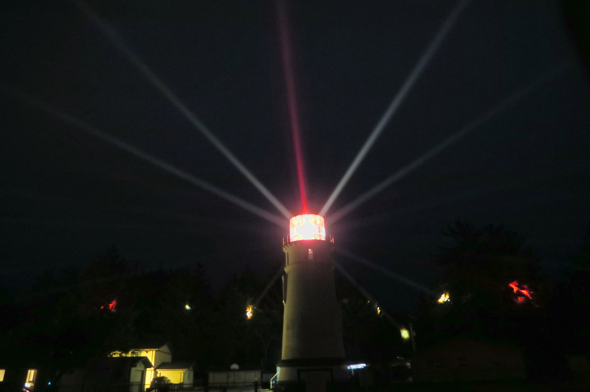 "The First Order Fresnel Lens has 22 bulls eyes which dictate the characteristic, or ""signature,"" which is 2 white flashes and 1 red flash every 15 seconds as the lens rotates. You can see the red and white ""spotlights"" reflecting in the trees in the background."