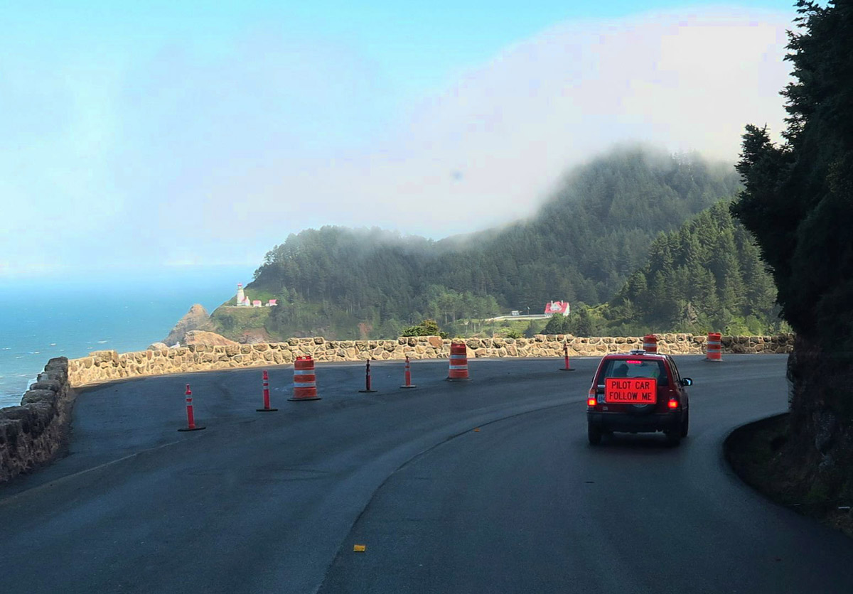 "A familiar sight on Hwy 101, the ""Follow Me"" Pilot Car. I am happily following to the scenic Heceta Head Lighthouse in the distance."