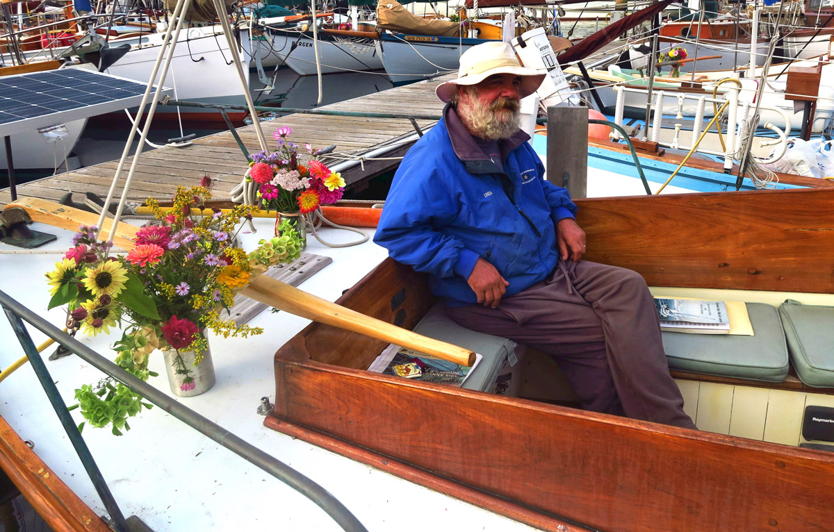 "I asked this gentleman if I could take his photo. I said ""You look like the quintessential ""salty ole sea dog"" to which he replied, ""You don't think the flowers give me away?"""