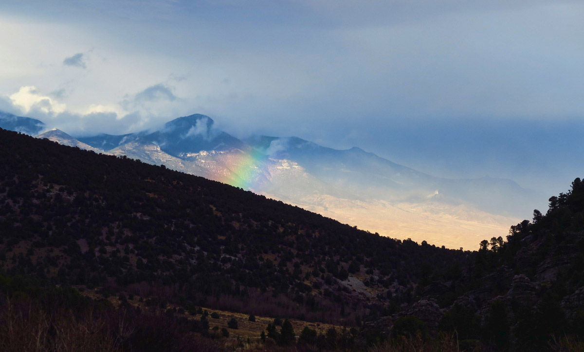 A smidgeon of a rainbow as the rain clears over the Great Basin desert.