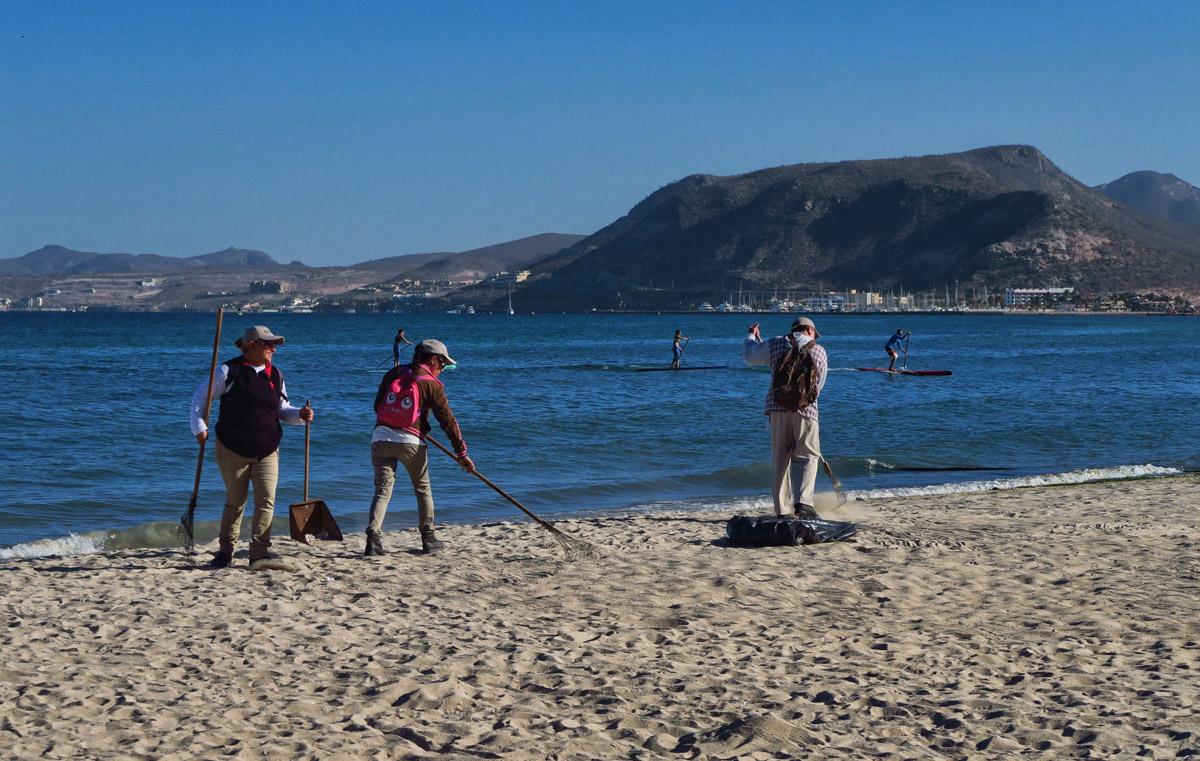 Raking the sand along the city shore while a paddleboard competition takes place on the water.