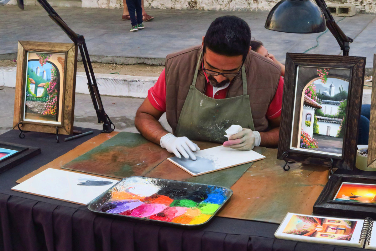 This gentleman is painting on tiles using only his fingers. Todos Santos Art Show.