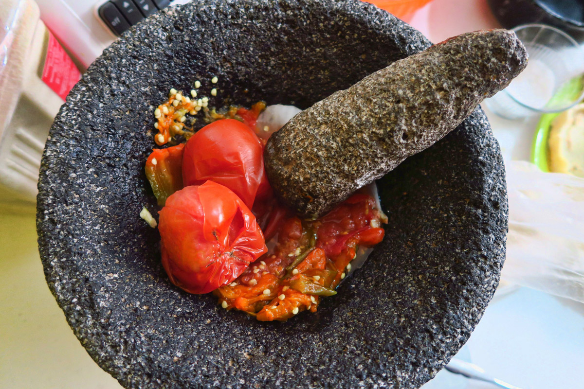 "To top the Sopes, we make warm ""Salsa Mocajete,"" named for the stone mortar and pestle. First, we boil the ""jitomate"" (tomato) and jalapeno. Then while still warm, smash them with onion, garlic, and cilantro to make a delicious salsa."