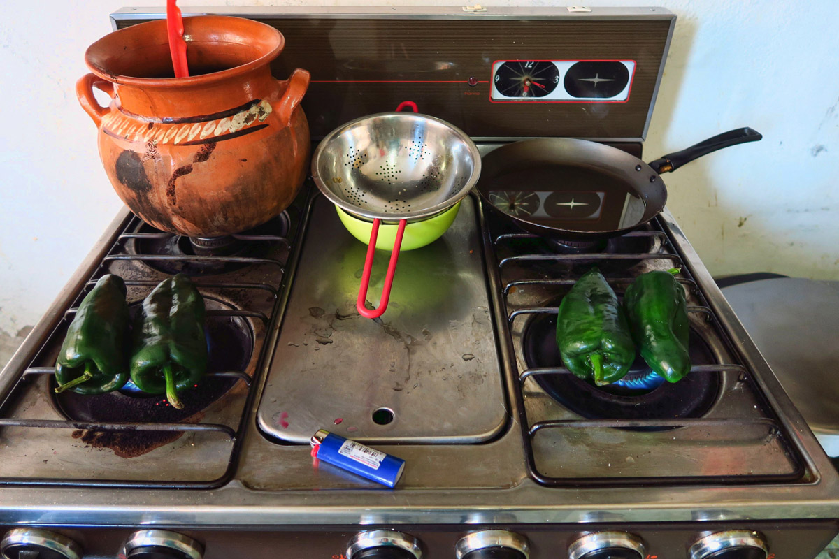 Roasting the poblano peppers right on the open flame.
