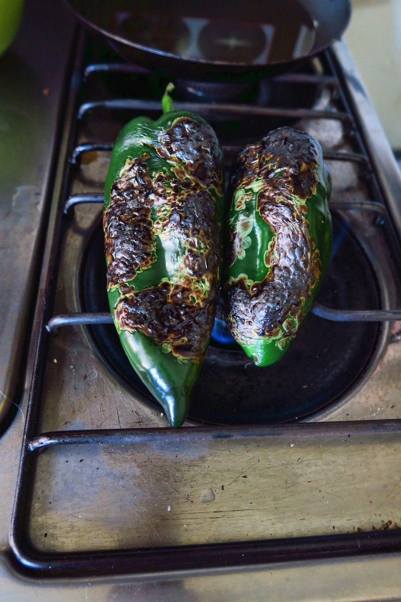 Fire roasted poblano peppers, blistered and almost ready to peel.