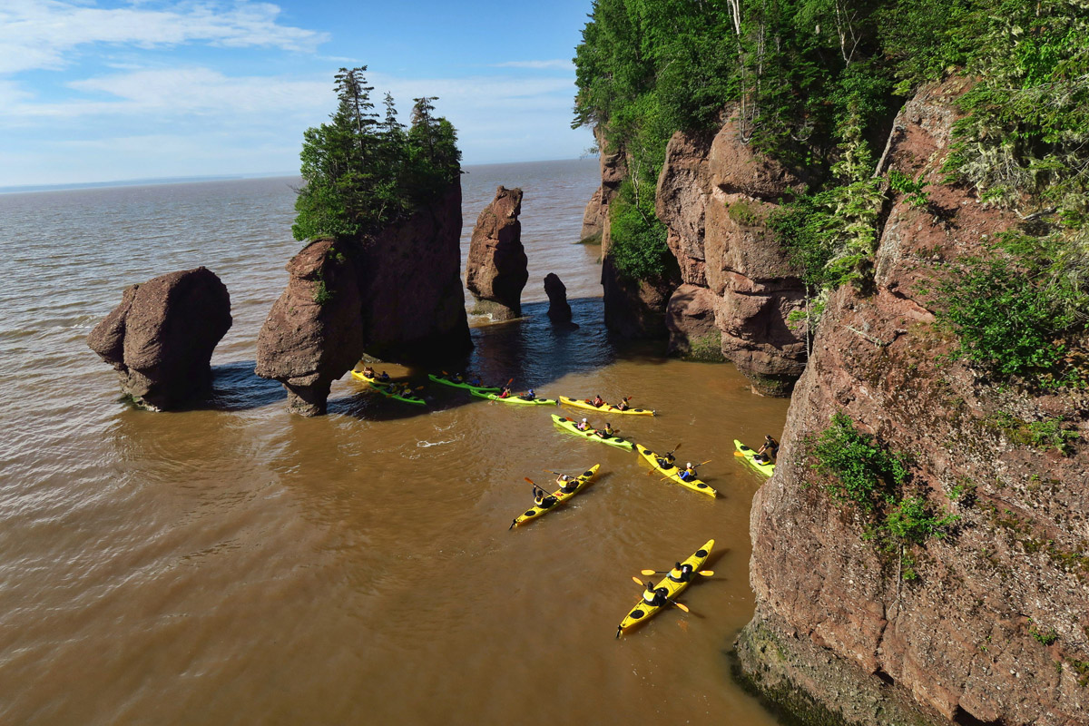 "Tours kayak through ""Lover's Arch,"" New Brunswick's most photographed attraction."