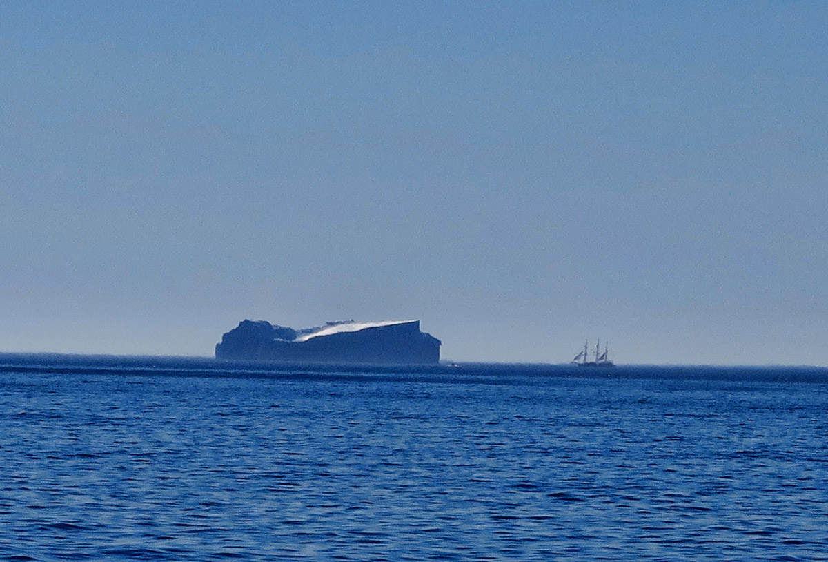 This is a terrible zoom photo, trying to take a picture five miles away, but that fuzzy spot to the right of the iceberg is the Lord Nelson Tall Ship, for scale.