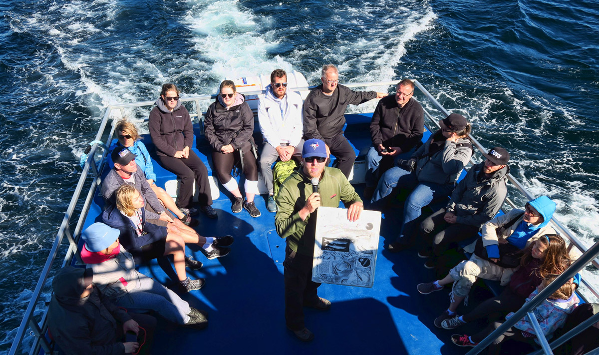 "Steve, our interpreter is telling us about feeding habits of whales. If you can see the two small fish in the dark square on the left, those are ""caplin,"" a very important part of the humpback diet. When the caplin start running, the whales follow. (Click to enlarge photo.)"