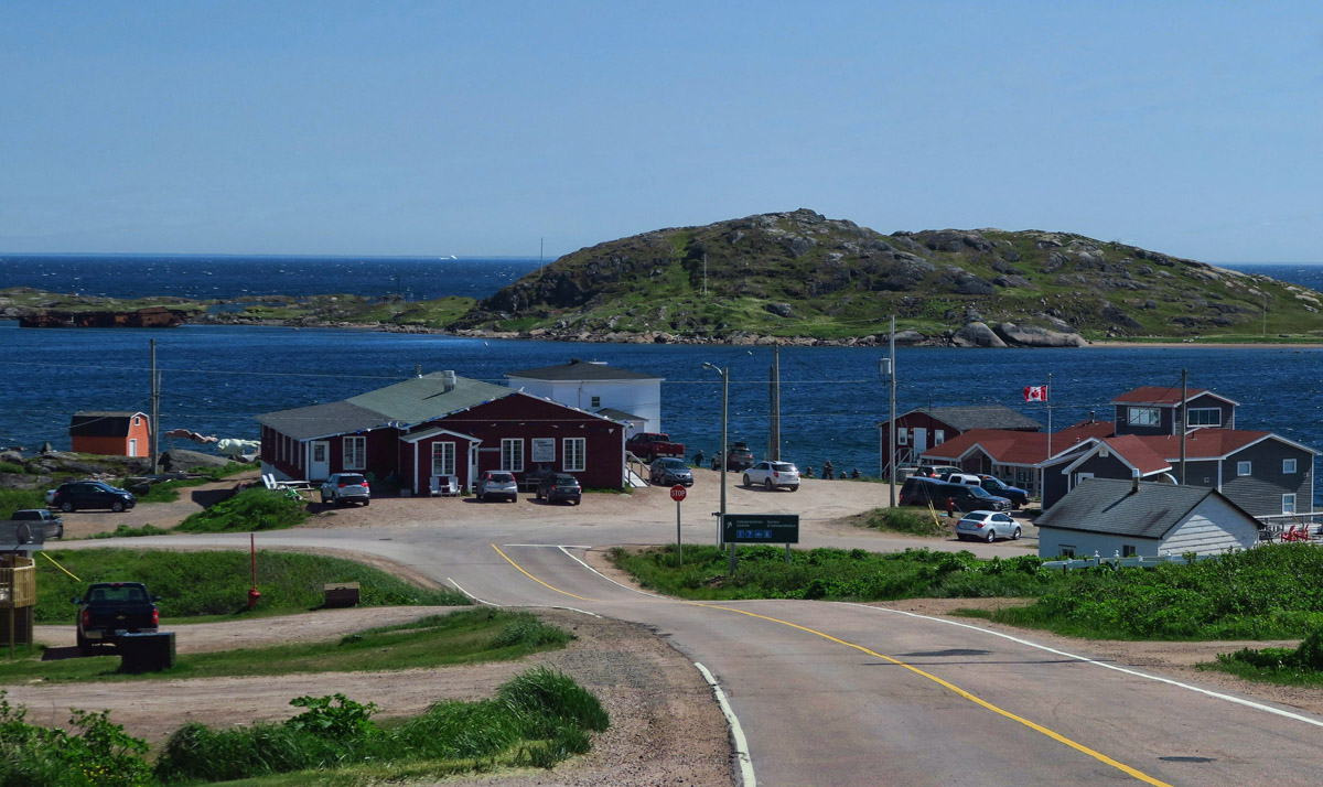"At the bottom of the hill is the Interpretive Center on the right, Saddle Island in the background, and Whaler's Restaurant on the left, which my friends Ed and Marti have tipped me off to ""best fish and chips in Labrador."""