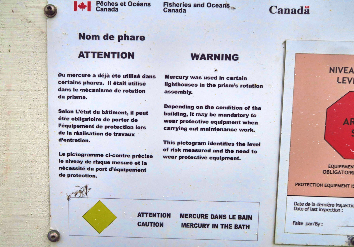 "Warning signs on the door to the lighthouse warning of ""Mercury in the bath."""