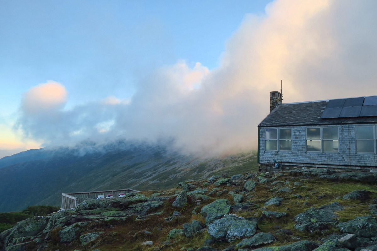 Awaking the next morning, the Lake of the Clouds hut reveals its namesake, as clouds pour over the mountains.