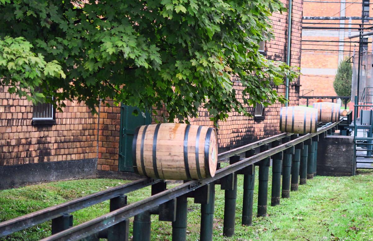Barrels roll on rales alongside warehouses.