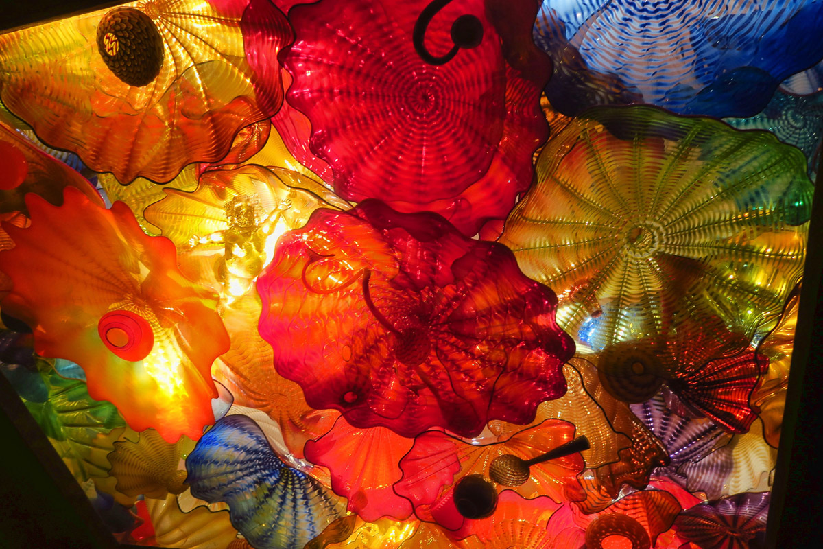 "This Chihuly art piece is behind glass on the ceiling. The piece contains four angels to represent the ""angel's share."" One can be seen in this section."