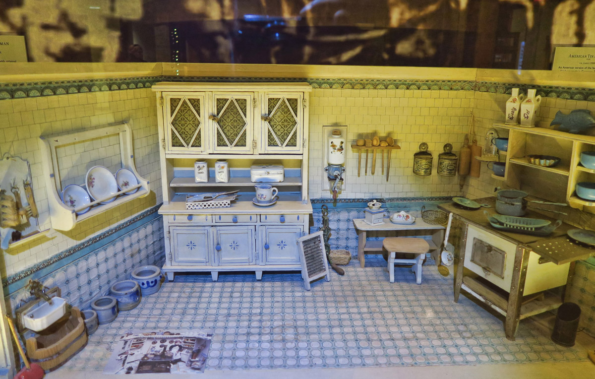 Nuremberg Turn of the Century Kitchen, 1909. Created prior to the 1970's, it does not follow the 1:12 miniature scale. Originally a child's toy rather than a collectable. Small water tank behind the wall allows water faucet in lower left to function, while stove could be heated by placing a candle inside.