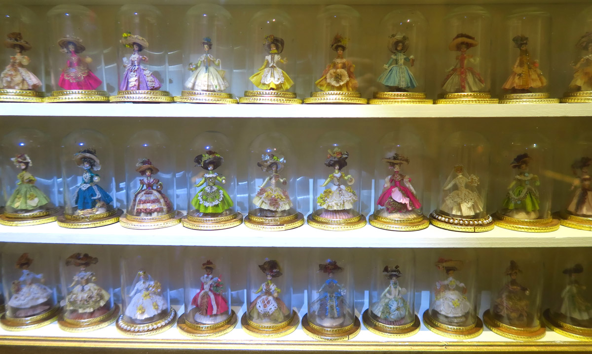 Fifty-two miniature dolls in original glass domes. Dolls are formed with a grain of wheat with painted features. Arms are thread wrapped around wire. Costumes are Swiss silk with dried plant accessories. Originally sold in Marshall Fields in Chicago in the early 1950's.